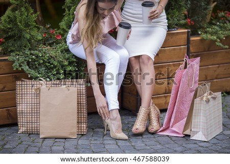 Two Girls Sit On A Bench Shopping Lot Of Bags Leg