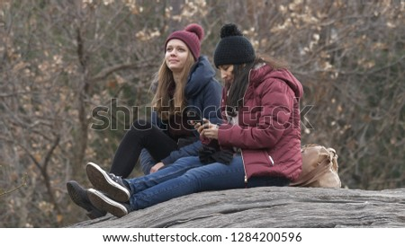 Stock Photo Two girls sit on a rock in Central Park New York
