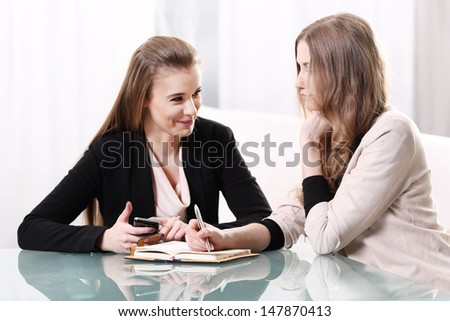 Two girls sitting and talking at a glass table - Shutterstock ID 147870413