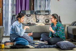 two girls sitting at home playing with cards