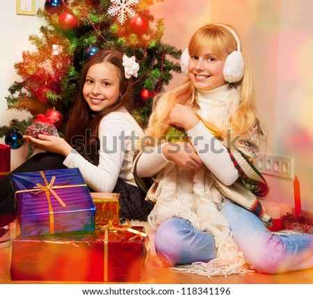 Two girls sitting near Christmas tree and holding their presents