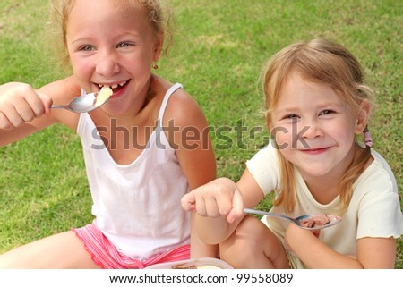 Two girls sitting on a green lawn and eat ice cream with a spoons - stock photo