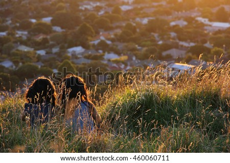 Two girls sitting on Mount Eden, Auckland, New Zealand. They are watching the sunset together and enjoy their friendship. The overexposed sun and underexposed friends set a cozy mood.