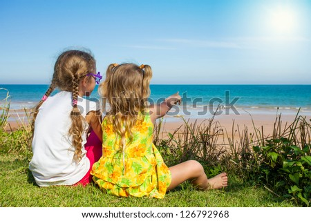 Two girls sitting on the beach and watching the sea