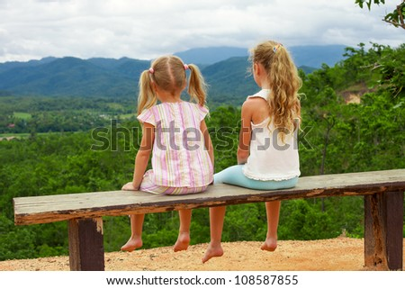 Two girls sitting on the bench against the backdrop of the mountains