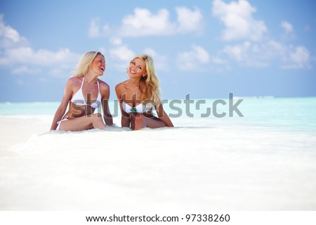 Two girls sitting on the ocean coast - stock photo