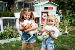 Two girls standing in front of hen house in a garden, holding white chickens, smiling at camera.