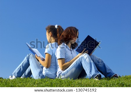 Two girls students sitting on grass studying in the nature reading books