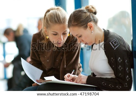 Two girls students studying together