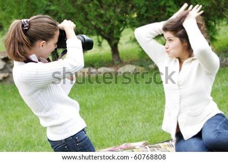 two girls taking pictures on nature