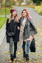Two girls talking to each other and laughing, autumn clothing