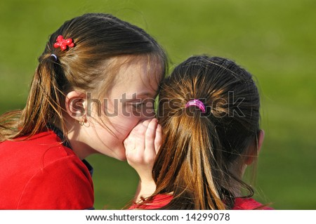 Two girls telling secrets outdoors at the park
