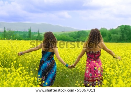 Two girls to keep for hands in a yellow field