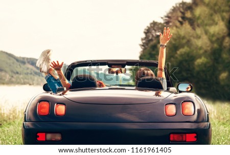 Two girls travelers sit in cabriolet car and enjoy with beautiful view