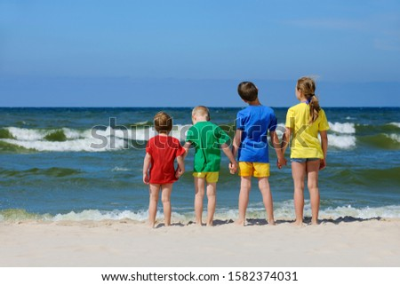 Two girls, two boys in colorful t-shirts standing back on a sandy beach and looking at the sea, blue sky in the background #1582374031