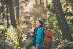 Two girls walk in the woods. Hiking in the mountains. Girlfriends spend time together in nature. Women walk in the park.