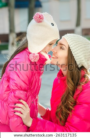Two girls walking  in the city.  Adult and child, mother and daughter, two sisters walk on the street, spring. Facial expression. Casual style, sportswear, pink jackets.