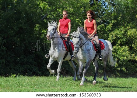 Two girls walking on horseback