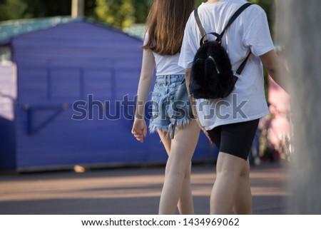 Two girls walking, ripped jeans short pants and cycling pants, fashion clothing trends #1434969062