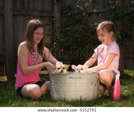 Two girls washing two Pomeranian puppies outside in an old tin tub.