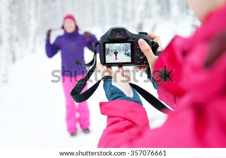 Two girls with a camera taking pictures in snow in winter in a park. Bright jacket. Photographer with the camera. Reflection on the screen