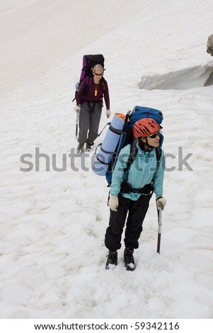 Two girls with backpackers on snow, looking where to go.