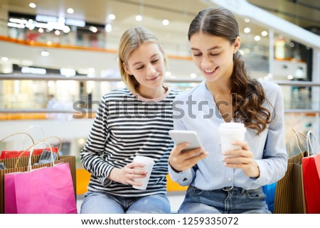 Two girls with drinks searching in online shops and comparing prices with those in offline departments
