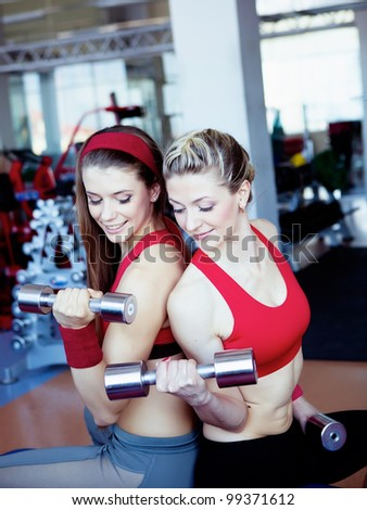 Two girls with dumbbells in hahds - stock photo