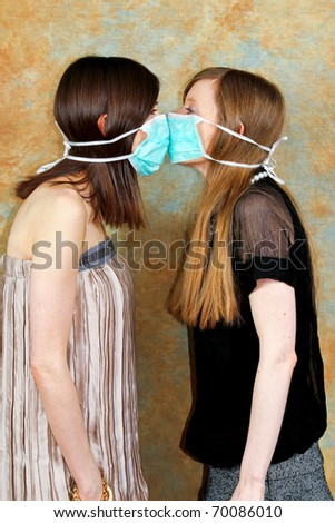 Two girls with protective masks against each other