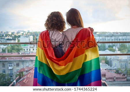 Two girls with rainbow flag looking out the window at the city. Lesbian couple celebrating pride month during Covid-19 quarantine, stay at home Foto stock ©