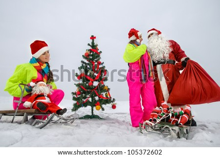 Two girls with Santa Claus decking up the Christmas tree at snow