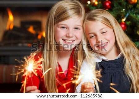 two girls with sparklers smiling #112665986