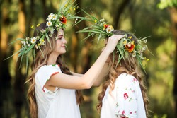 Two girls with wreaths of flowers in their hands. Midsummer. Earth Day.