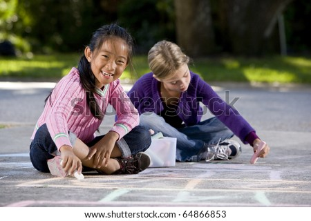 Two girls, 7 years, drawing pictures on driveway with chalk