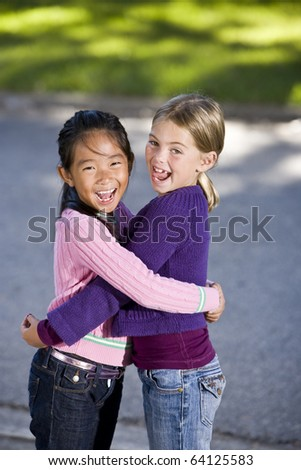 Two girls, 7 years, hugging and laughing