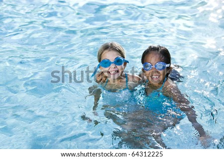 Two girls, 7 years, wearing swim goggles playing together in swimming pool