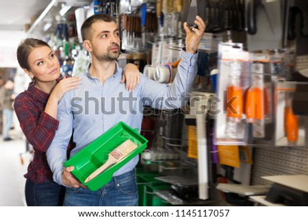 Two glad designer are choosing putty knife for redecorate room in the store
