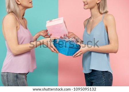Two glad women standing one against another and exchanging present boxes. blue and pink background