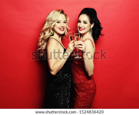 Two glamour women, girlfriends in luxury glitter sequins dress and bright visage posing over red background