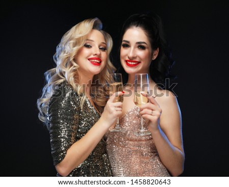 Two glamour women in luxury glitter sequins dress drinking champagne and having fun