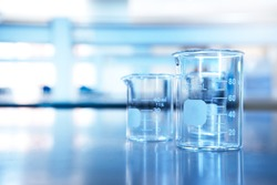 two glass beaker on chemistry science laboratory table blue research and education background