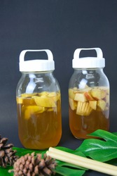 Two glass bottle filled with sucrose solution in brown colour and sliced tropical fruits such as mangos, Jicama and rose apple for preparation of Kambucha homemade probiotic drink.