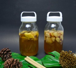 Two glass bottles are filled with sucrose solution in brown colour and sliced tropical fruits such as mangos, Jicama and rose apple for preparation of Kambucha homemade probiotic drink.