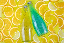 Two glass bottles on a bright tropical citrus background. Blue and yellow drinks with seeds. Orange slices, fruit smoothie. Beverage in water. Summer lemonade with drops. Soft drink, juice. Thirst.