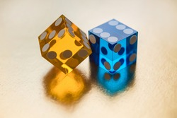 Two glass dice, blue and yellow, on a gold background in sunlight. Result six and unknown. Selective focus macro photography. Luck concept.