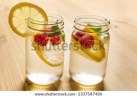 two glass jars with cold water, slices of lemon, mint and red berries, illuminated by sunlight on a wooden table with some pieces of citrus, summer refreshments background, copy space #1337587406