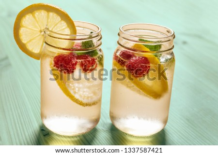 two glass jars with cold water, slices of lemon, mint and red berries, illuminated by sunlight on a green wooden table with some pieces of citrus, summer refreshments background, copy space #1337587421