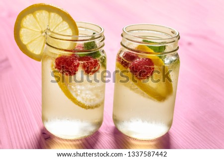 two glass jars with cold water, slices of lemon, mint and red berries, illuminated by sunlight on a pink wooden table with some pieces of citrus, summer refreshments background, copy space #1337587442