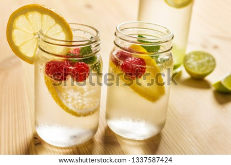 two glass jars with cold water, slices of lime, lemon, mint and red berries illuminated by sunlight on a wooden table with a bottle and pieces of citrus, summer refreshments background, copy space #1337587424
