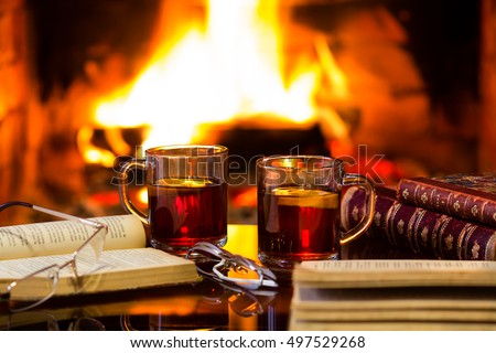 Two glass mugs of hot drink or alcoholic drink or mulled red wine and antique books in front of warm fireplace. Magical relaxed cozy atmosphere near fire. Autumn or winter concept